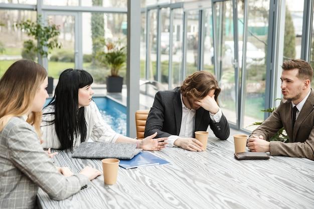 Quatro pessoas estão sentadas na sala de reuniões