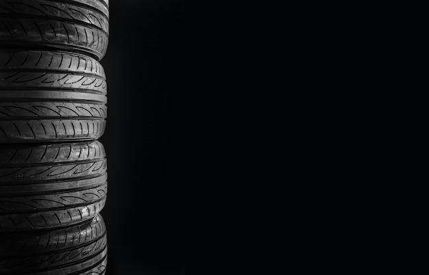Quatro pneus de carro isolados no espaço livre do fundo preto no lado direito para o texto.