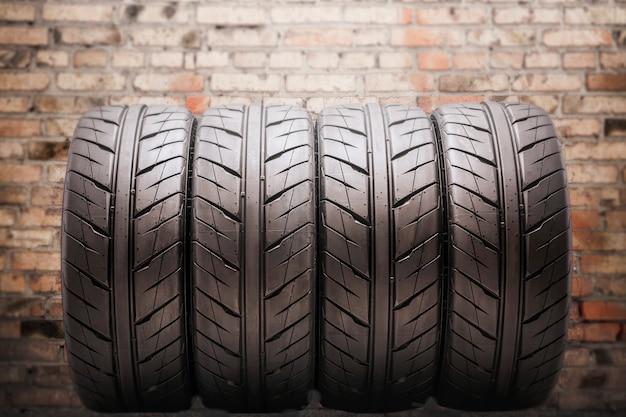 Quatro pneus de verão, com canais de drenagem, cofre muito bonito e moderno, contra o fundo da parede de tijolos da garagem. auto tuning e peças de reposição