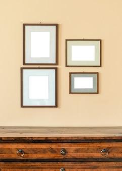 Quatro porta-retratos vazios de tamanhos diferentes exibidos na parede acima de uma placa de madeira pronta para a colocação de suas obras de arte ou fotos