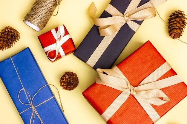 Quatro presentes multicoloridos e barbante de embalagem estão sobre uma superfície amarela. vista de cima.