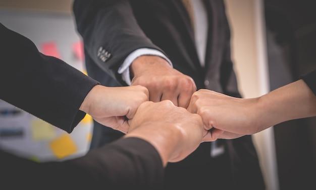 Quatro punho colidir na reunião de negócios para o conceito de equipe