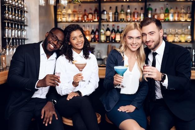 Quatro rapazes e raparigas bebem cocktails num bar.
