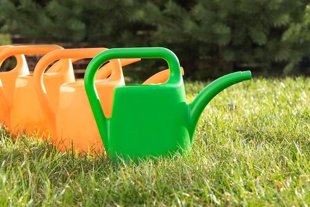 Quatro regadores de cores vivas, três laranja e um verde, estão alinhados no gramado. preparando-se para jardinagem na primavera. o conceito de jardinagem primavera. fundo com efeito de desfoque.