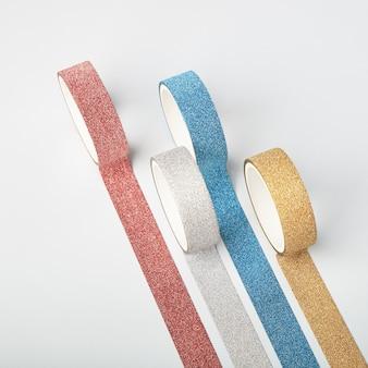 Quatro rolos de fita de glitter e tiras paralelas na mesa branca