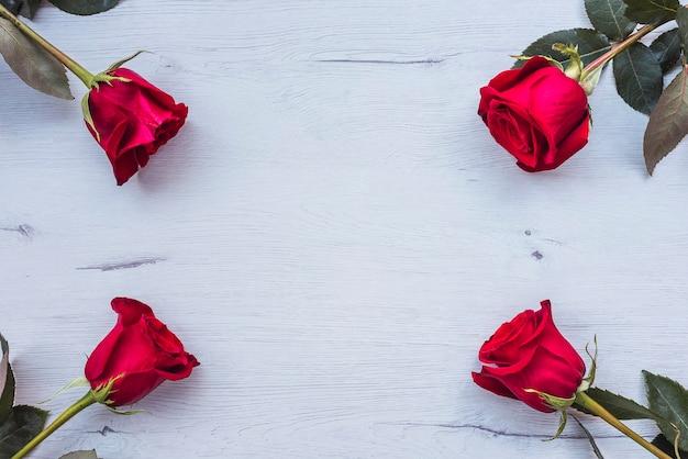 Quatro rosas vermelhas na mesa de madeira, copie o espaço