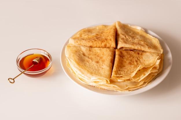 Quatro saborosas panquecas apetitosas dobradas em uma pilha de outras em um prato de porcelana branca e uma pequena tigela de vidro com mel fresco perto