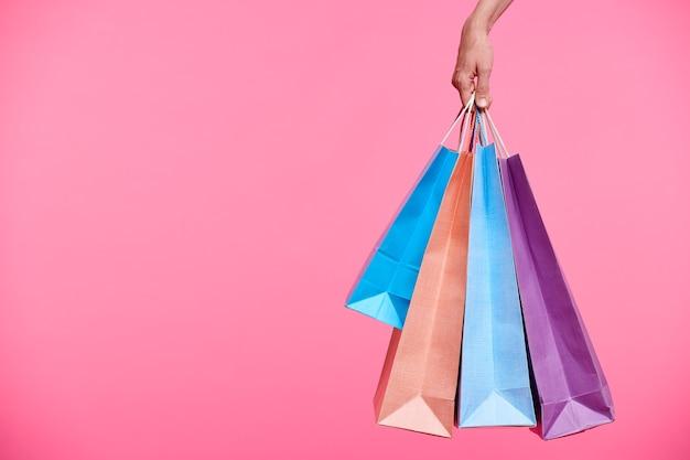 Quatro sacolas de papel coloridas seguradas pela mão de uma shopaholic enquanto as carregava após as compras