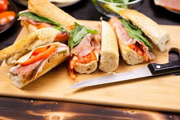Quatro sanduíches caseiros em uma placa de madeira em uma foto de estúdio