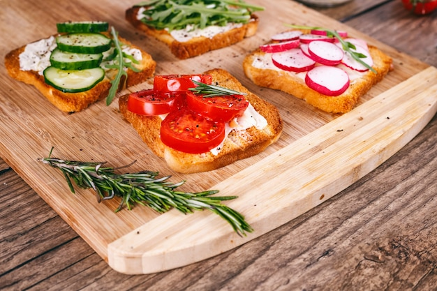 Quatro sanduíches com legumes frescos, tomates, pepinos, rabanete e rúcula em um fundo de madeira