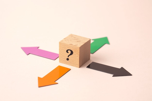 Quatro setas de direção com ponto de interrogação no cubo de madeira