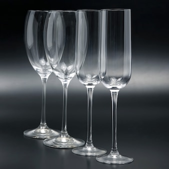Quatro taças de vinho em um close-up de fundo escuro. talheres para bebidas