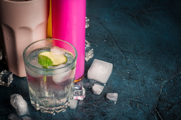 Quatro tipos de bebidas refrescantes com gelo em uma superfície azul escura e cubos de gelo.