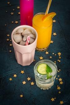 Quatro tipos de bebidas refrescantes com gelo em uma superfície azul escura e estrelas.