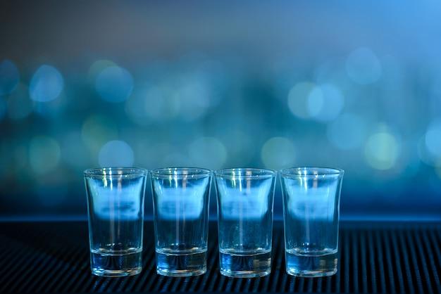 Quatro tiros de tequila em uma barra de mesa de madeira.