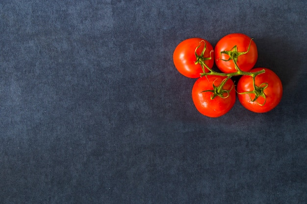 Quatro tomates vermelhos na mesa azul, vegetal
