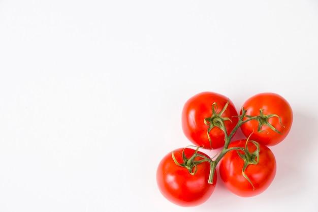 Quatro tomates vermelhos na mesa branca, vegetais