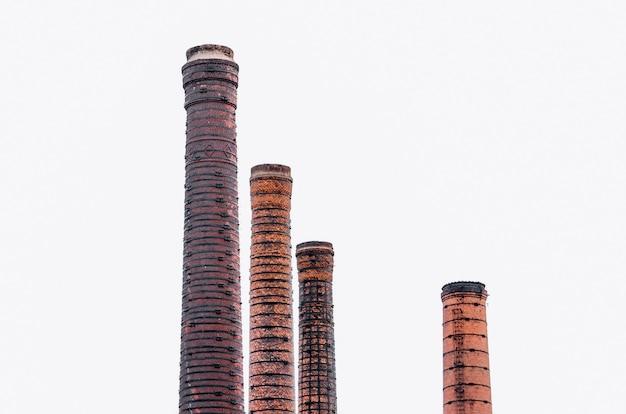 Quatro tubos altos de tijolo vermelho, chaminé de fábrica.