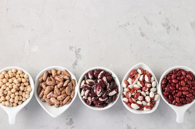 Quatro variedades de feijão e grãos ricos em proteínas do grão de bico estão localizadas no fundo cinza de concreto