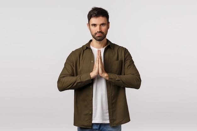Que a força esteja com você. confiante e paciente homem barbudo bonito praticar yoga, pressione as palmas das mãos juntas namaste, orando gesto sorrindo pacífica e relaxada, meditando, curvando-se educadamente
