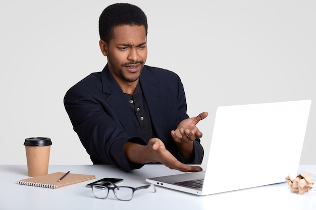 Que absurdo! o descontentamento afro-americano insatisfeito confuso do homem negro com figuras financeiras no projeto do negócio, indica com as mãos no sceen, sente-se irritado, isolado no branco.