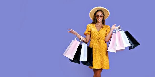 Que bom que a garota de chapéu e óculos escuros faz compras enquanto sorri para a câmera preta nas grandes vendas de sexta-feira
