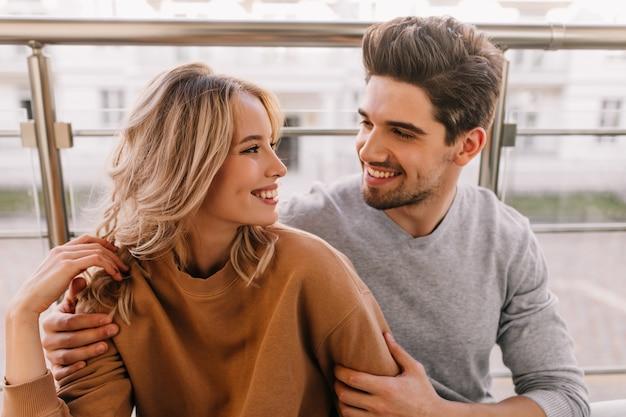 Que bom que cara abraçando a namorada. retrato de casal caucasiano, sorrindo um para o outro.