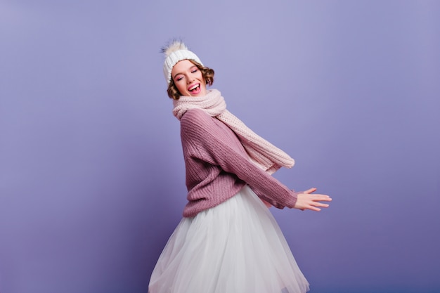 Que bom que garota com cabelo curto e brilhante, posando com um lindo chapéu branco. dançando atraente modelo feminino com saia e lenço de malha.