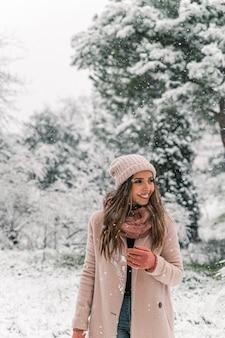 Que bom que mulher com roupas quentes em pé em um bosque nevado olhando para longe enquanto aproveita o fim de semana de inverno