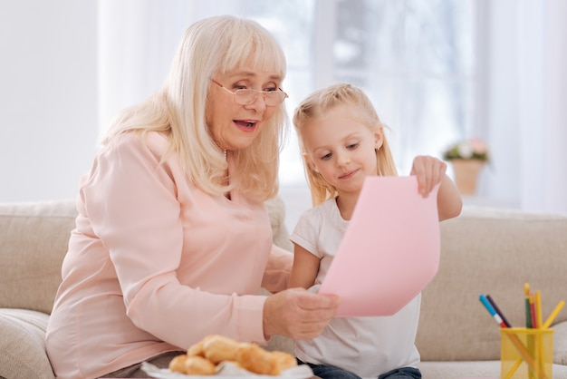 Que criativo. mulher idosa encantada positiva usando óculos e olhando para as netas desenhando enquanto desfruta de sua criatividade
