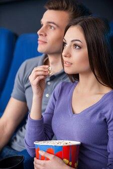 Que filme emocionante! casal jovem animado comendo pipoca enquanto assiste a um filme no cinema