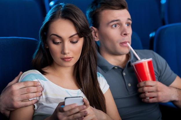 Que filme emocionante! jovem casal animado comendo pipoca e bebendo refrigerante enquanto assiste a um filme no cinema