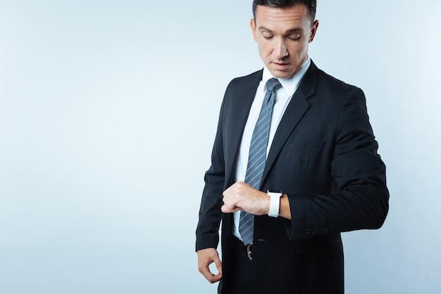Que horas são. confiante, ocupado, bonito, olhando para o relógio e verificando as horas enquanto tem um compromisso
