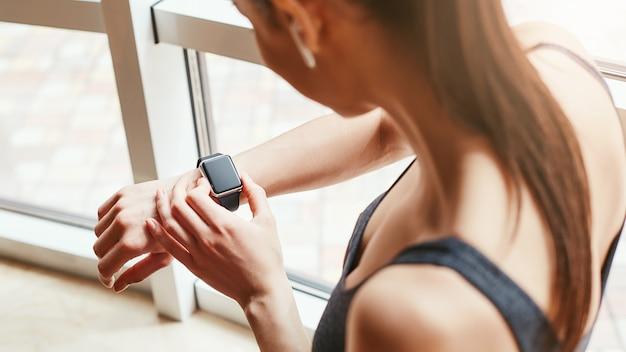 Que horas são foto recortada de mulher jovem em roupas esportivas verificando as horas