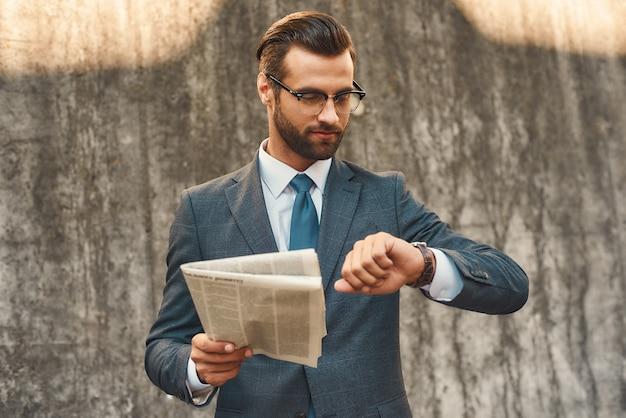 Que horas são jovem e bonito empresário barbudo de óculos verificando as horas e