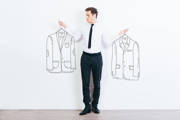 Que jaqueta devo escolher? jovem bonito escolhendo entre duas jaquetas desenhadas em pé contra um fundo branco