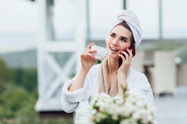 Que tal café no ar fresco, falando por telefone. relaxando no terraço de luxo villa com xícara de café ou chá.
