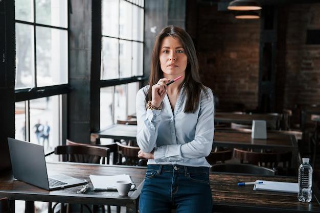 Que tipo de problema precisamos resolver hoje. mulher de negócios com roupas oficiais está dentro de casa no café durante o dia.