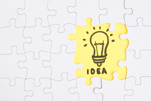 Quebra-cabeça amarelo idéia destacam-se das peças brancas