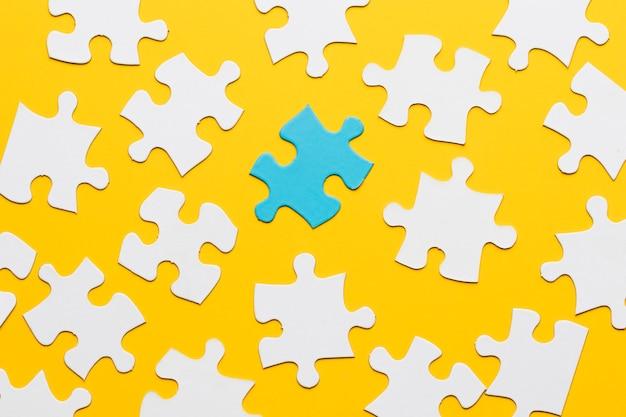 Quebra-cabeça azul com peça de quebra-cabeça branca em fundo amarelo