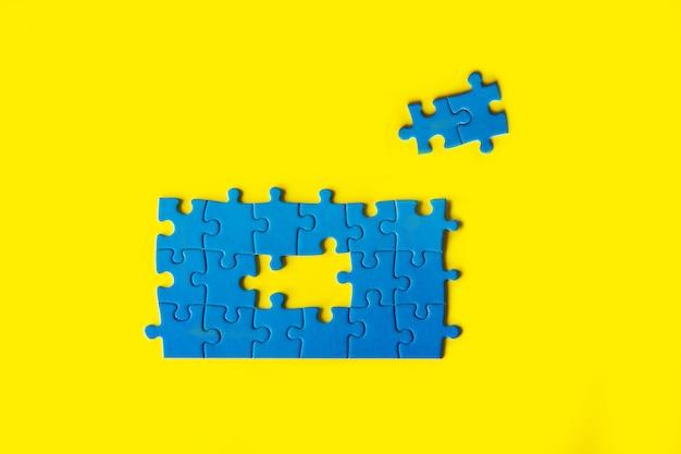 Quebra-cabeça azul sobre fundo amarelo, conexão de negócios, conceito de sucesso e estratégia, trabalho em equipe