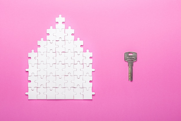 Quebra-cabeça branca. chave e quebra-cabeça de forma de casa. o conceito de aluguel, hipoteca. vista do topo