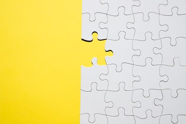 Quebra-cabeça branca com uma peça que faltava no pano de fundo amarelo