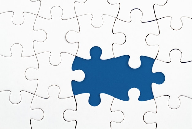 Quebra-cabeça branca sobre fundo azul com peças faltando. elementos incompletos, conceito de pesquisa de solução