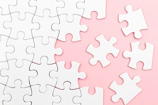 Quebra-cabeça branca sobre fundo rosa com peças faltando. elementos incompletos, conceito de pesquisa de solução