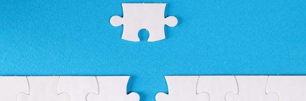 Quebra-cabeça branco inacabado perto da última peça no fundo azul close-up