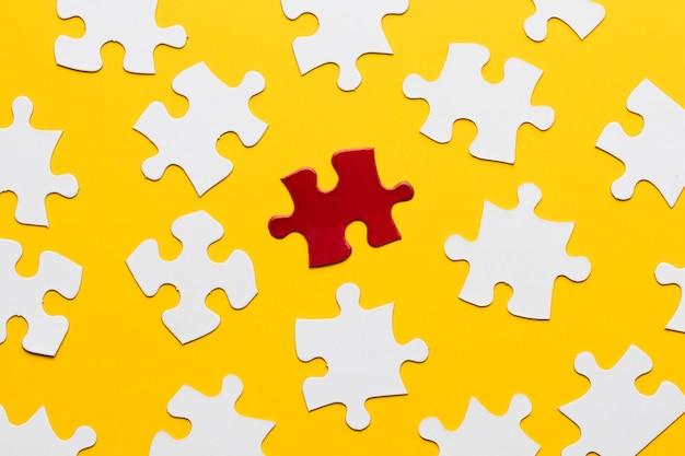 Quebra-cabeça brilhante vermelho entre branco contra pano de fundo amarelo