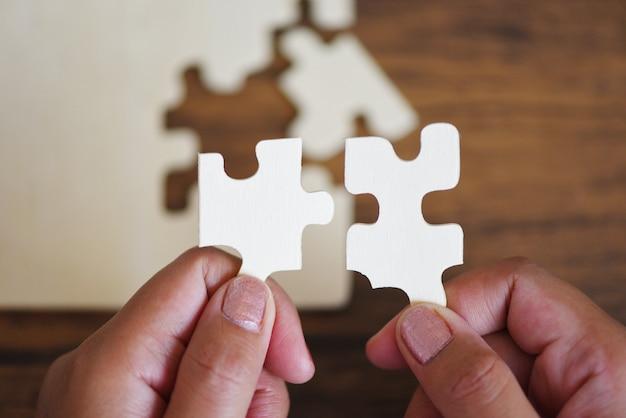 Quebra-cabeça com mão de mulher, conectando a peça de quebra-cabeça
