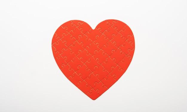 Quebra-cabeça de cor vermelha em forma de coração em fundo branco
