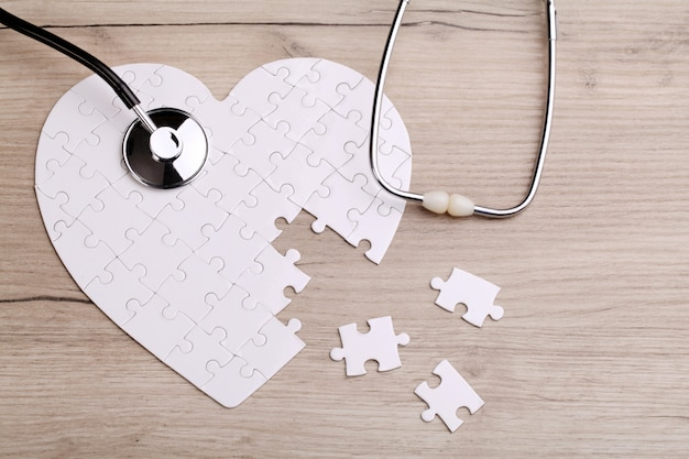 Quebra-cabeça de forma de coração branco com estetoscópio
